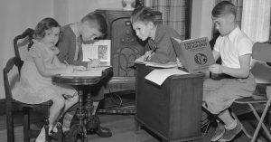 Children sitting around a radio for school lessons in 1937
