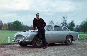 James Bond leaning against his Aston Martin D5B