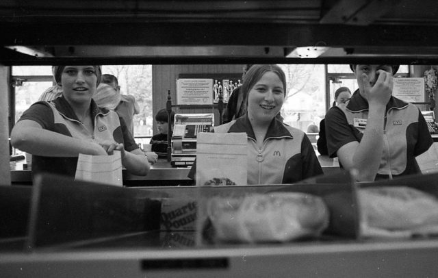 Three female McDonald's employees bagging hamburgers