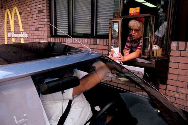 Woman handing a man a soda at a drive-thru window