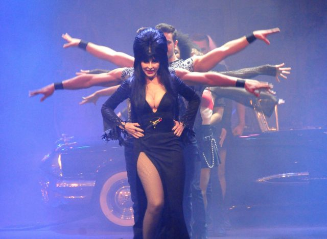 "Elvira, aka Cassandra Peterson performs her new show ""Elvira, Mistress Of The Dark"" on September 21, 2017. (Photo Credit: Barry King/Getty Images)"
