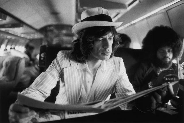 Mick Jagger reading between concerts, 1975