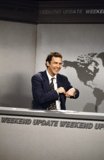 "Norm Macdonald sitting behind the ""Weekend Update"" desk"