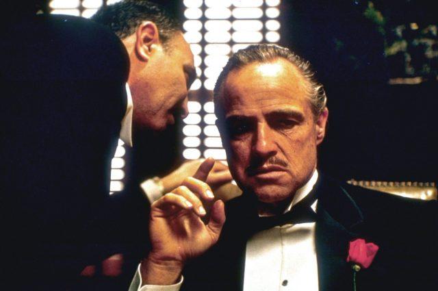 Amerigo Bonasera speaking into Don Corelone's ear